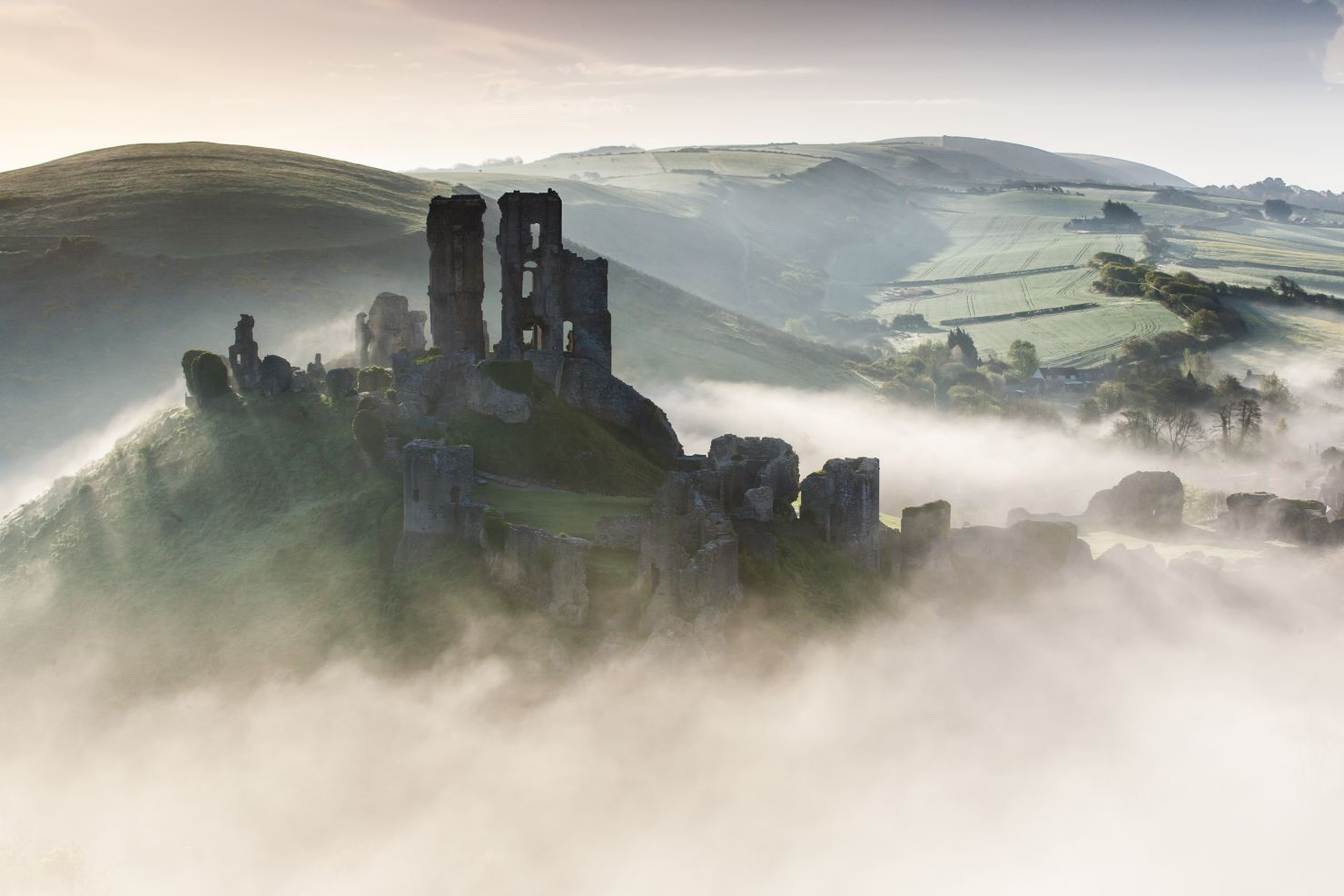 Ruins of Corfe Castle rising from above the fog
